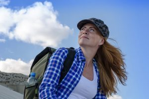 Young beautiful woman backpacker with red hair and freckles traveling in the desert. Sandy dunes and blue sky on sunny summer day. Travel, adventure, freedom concept. Toned.