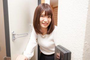 Young woman opening door of her room