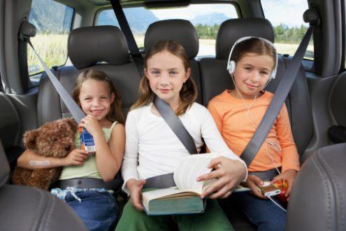 Three girls (6-8 years) sitting on rear seat of car, smiling, portrait