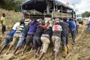 Des locaux poussent un camion après qu'il s'est enlisé alors qu'il traversait la province Ouest.