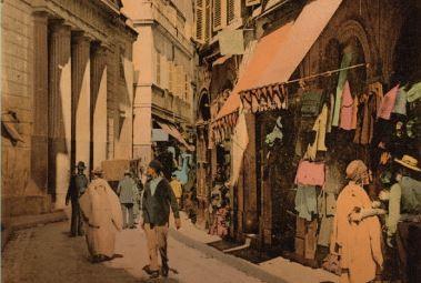 Une rue d'Algérie, un temple protestant à colonnades en arrière plan, la rue est bordée d'échoppes