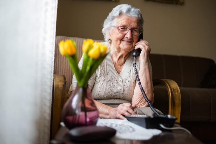 Une dame âgée est au téléphone avec en avant-plan des tulipes jaunes dans un vase