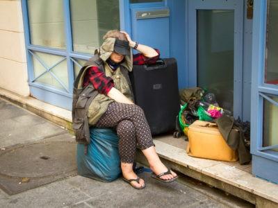 Une femme sans domicile fixe avec des sacs et une valise sur un trottoir à Paris