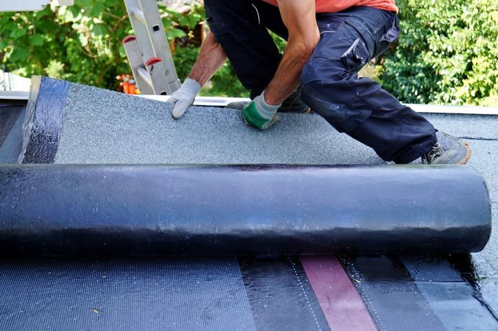 Ouvrier installant du papier goudronné sur le toit d'un bâtiment. Installation sur un toit plat. Système d'étanchéité au gaz et au chalumeau.