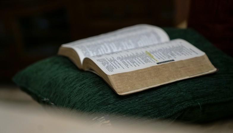 Bible ouverte sur un coussin vert