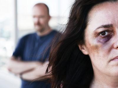 Une femme triste avec un bleu à l'oeil et un homme en arrière-plan