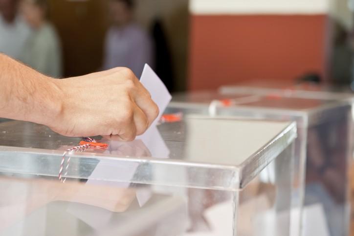 Une main tient un bulletin de vote au dessus d'une urne transparente