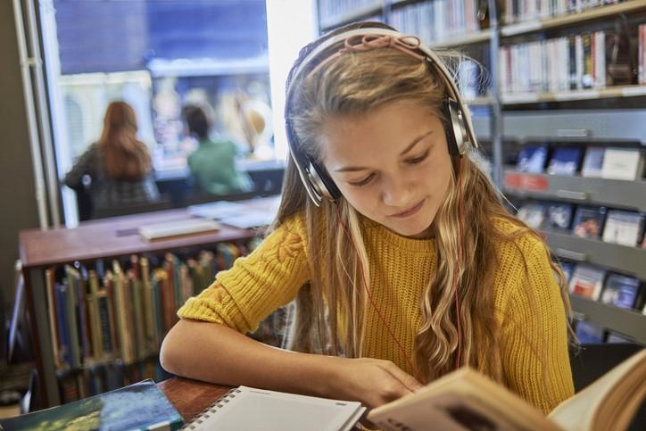 Une jeune fille avec des écouteur, les cheveux longs blonds et un pull jaune lit un livre dans une bibliothèque