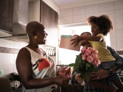 Une mère accepte le cadeau de son fils tenu dans les bras de son père