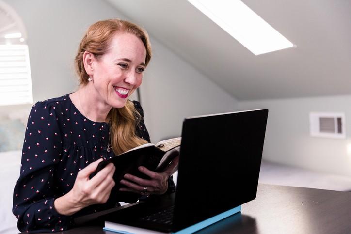Une femme habillée ne robe bleu marine à poids blancs, cheveux roux, une bible ouverte dans les mains, regarde son écran d'ordinateur avec le sourire Elle est dans une chambre nue aux murs blancs sous les toits.