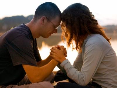 Couple priant ensemble au lever du soleil au bord d'un lac