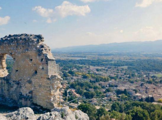 Un pan de mur en ruine avec une fenêtre surplombe une vallée du Lubéron très peu urbanisée